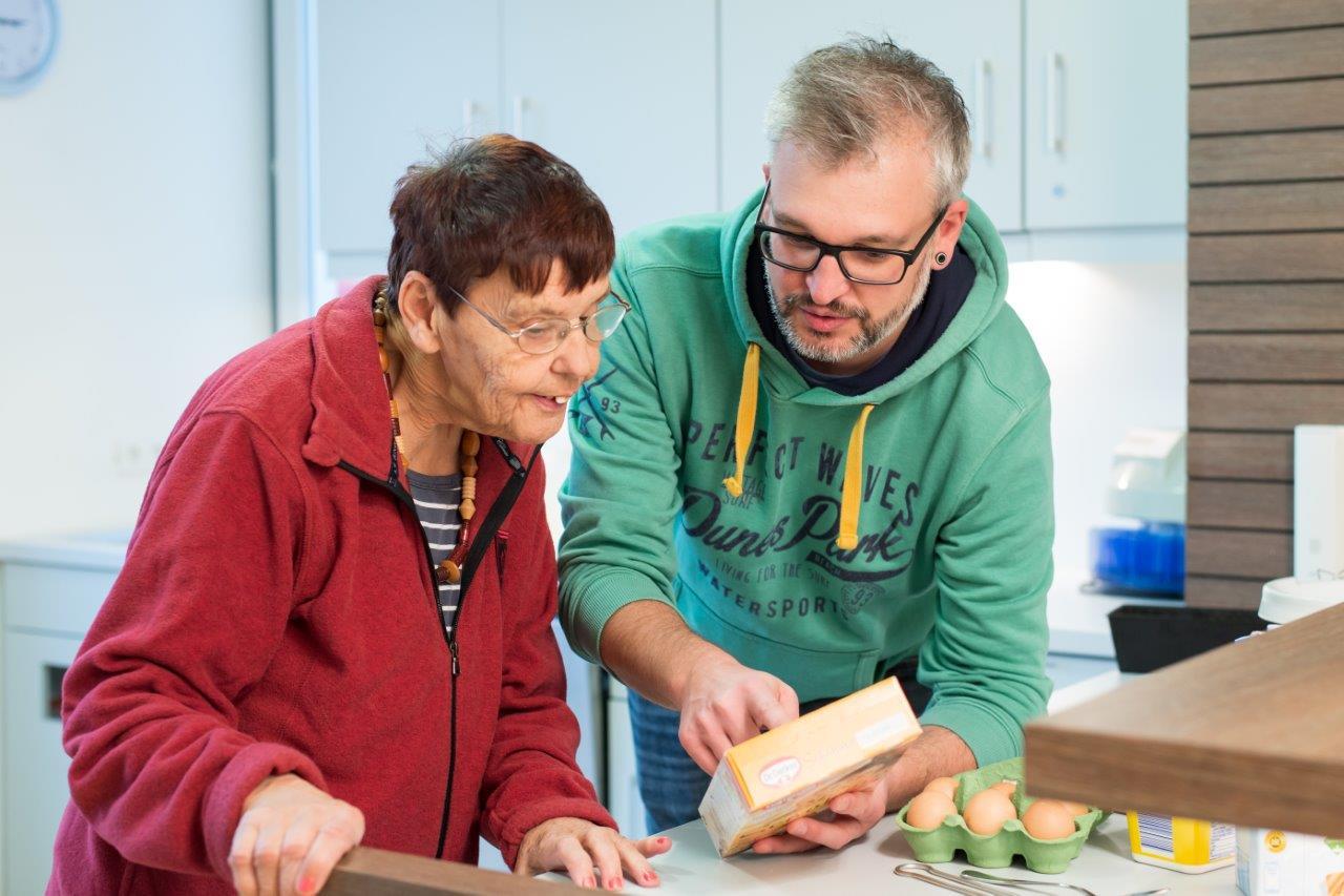 Ein Heilerziehungspfleger backt mit einer Klientin