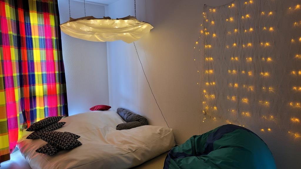 Eine Liegelandschaft mit einer beleuchteten Wolke an der Decke, Lichtern auf der Wand und bunten Gardinen